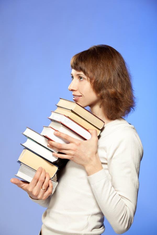 La mujer joven sonriente que sostiene una pila de libros foto de archivo