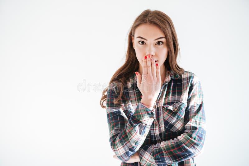 La mujer joven sorprendente feliz cubrió su boca a mano foto de archivo libre de regalías