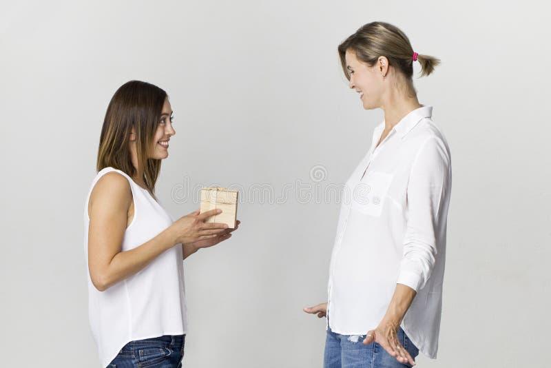 La mujer joven sorprendida consigue un regalo de su amigo Amigos femeninos felices y sonrientes imagen de archivo libre de regalías