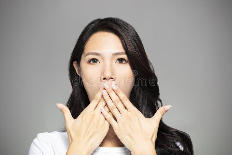 La mujer joven sorprendida da a coverd la boca fotografía de archivo libre de regalías