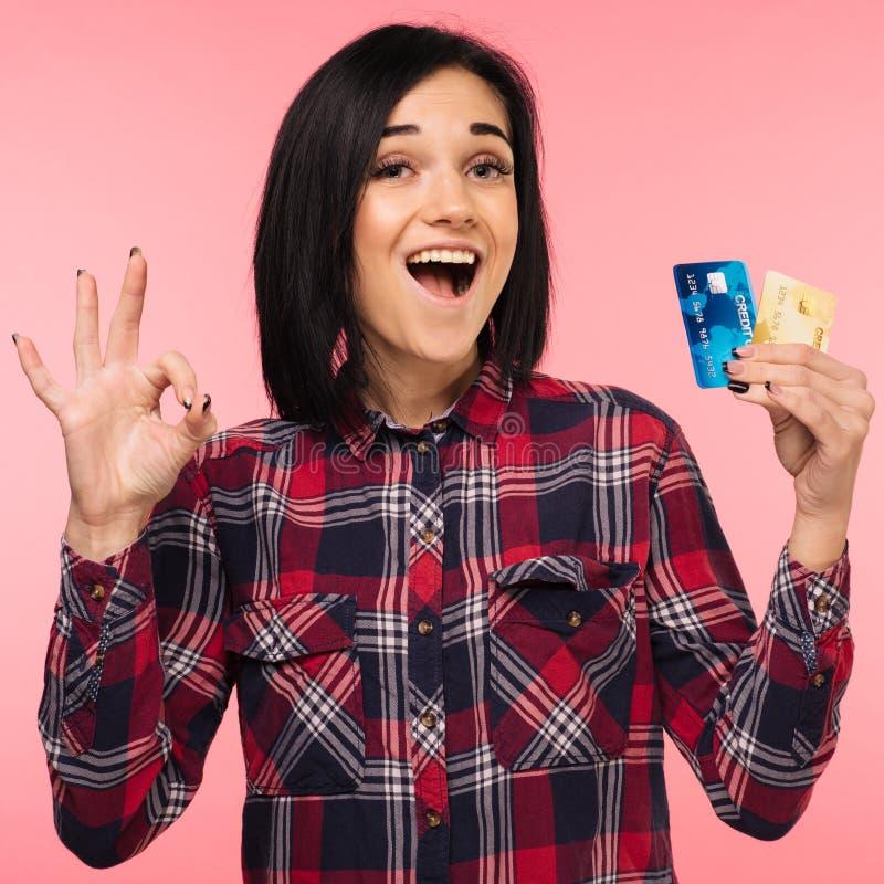 La mujer joven sorprendida emocionada alegre con la demostración de la tarjeta de crédito canta muy bien sobre fondo rosado fotos de archivo libres de regalías