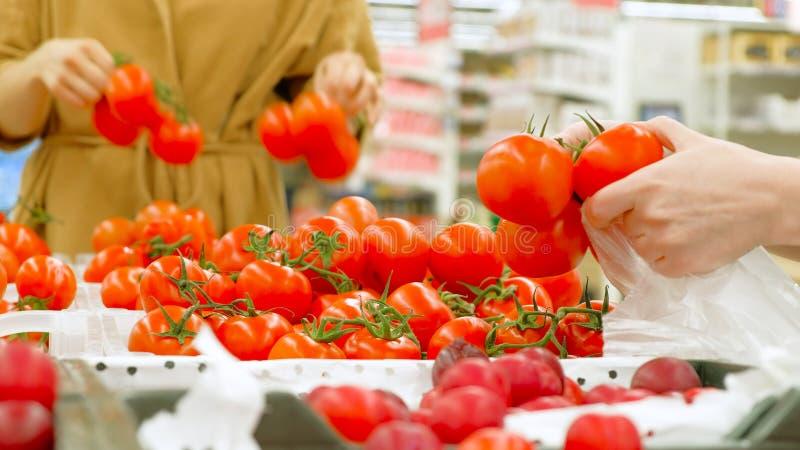 La mujer joven sostiene la bolsa de plástico blanca y elige los tomates imagen de archivo