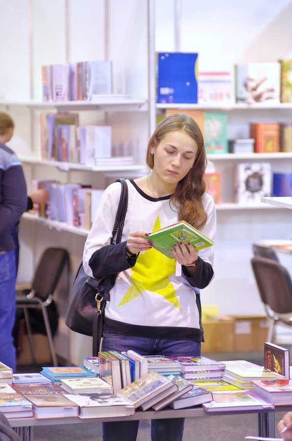 La mujer joven sostiene el libro y mira fotos de archivo