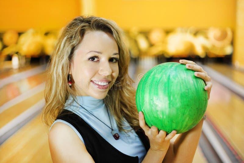 La mujer joven sostiene la bola en club del bowling imagen de archivo