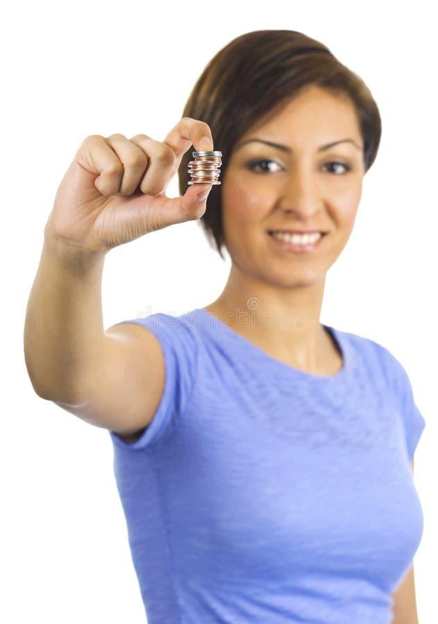 La mujer joven sostiene monedas entre sus dedos foto de archivo