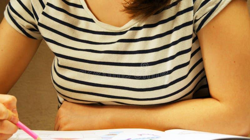 La mujer joven sostiene un lápiz y dibuja en casa Colorante para los adultos y los niños Para el alivio de tensión Libro de color imágenes de archivo libres de regalías