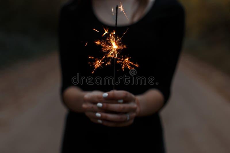 La mujer joven sostiene una bengala festiva anaranjada brillante en sus manos La muchacha celebra cumpleaños La hembra da el prim foto de archivo