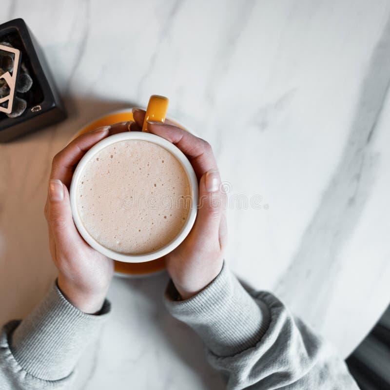 La mujer joven sostiene una taza de americano caliente delicioso con leche mientras que se sienta en una cafetería del vintage Ga foto de archivo libre de regalías