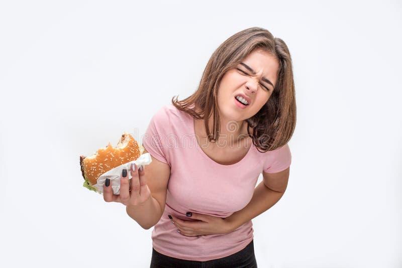 La mujer joven sufre de dolor en estómago Ella sostiene la hamburguesa mordida Otra mano está en área del estómago Aislado en bla imagenes de archivo