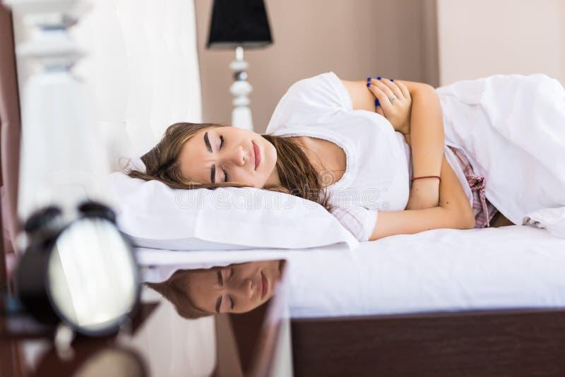 La mujer joven tiene dolor de la menstruación o dolor de estómago en la cama fotografía de archivo libre de regalías