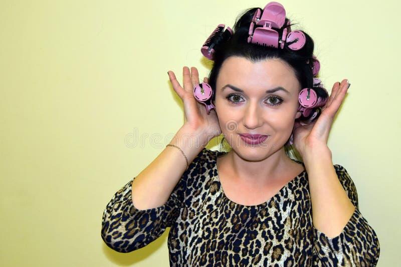 La mujer joven tiene las cerraduras del pelo que se aspan para arriba en los bigudíes de pelo fotografía de archivo