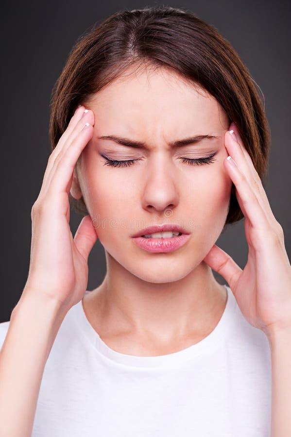 La mujer joven tiene un dolor de cabeza fotos de archivo