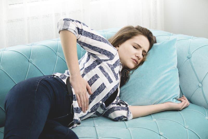 La mujer joven tiene un dolor de estómago en el sofá en casa fotos de archivo libres de regalías