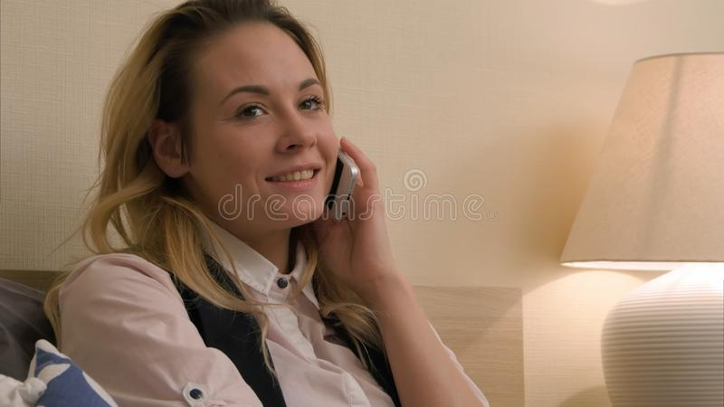 La mujer joven tiene una conversación positiva usando el teléfono móvil que se sienta en cama imagen de archivo libre de regalías