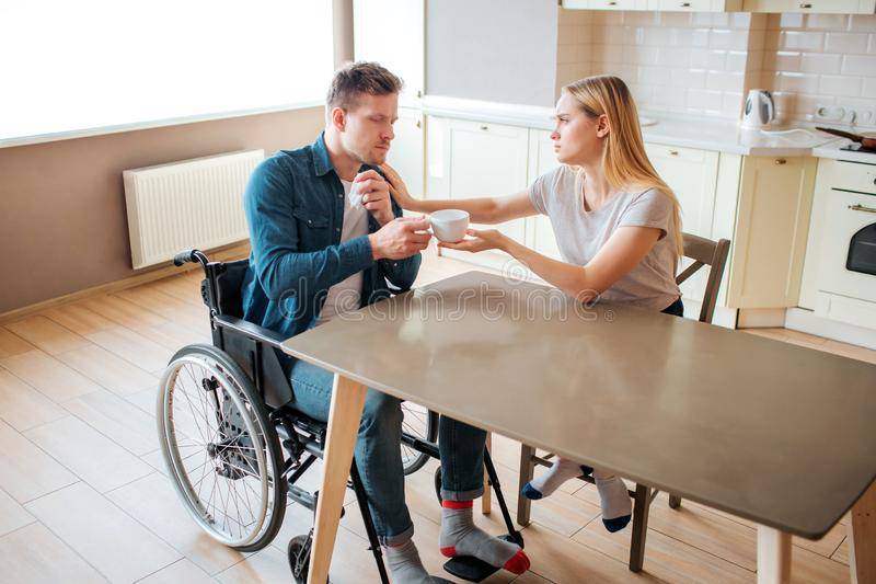 La mujer joven toma el cuidado del hombre con necesidades especiales ?l se sienta en la silla de ruedas y consigue la taza de beb foto de archivo