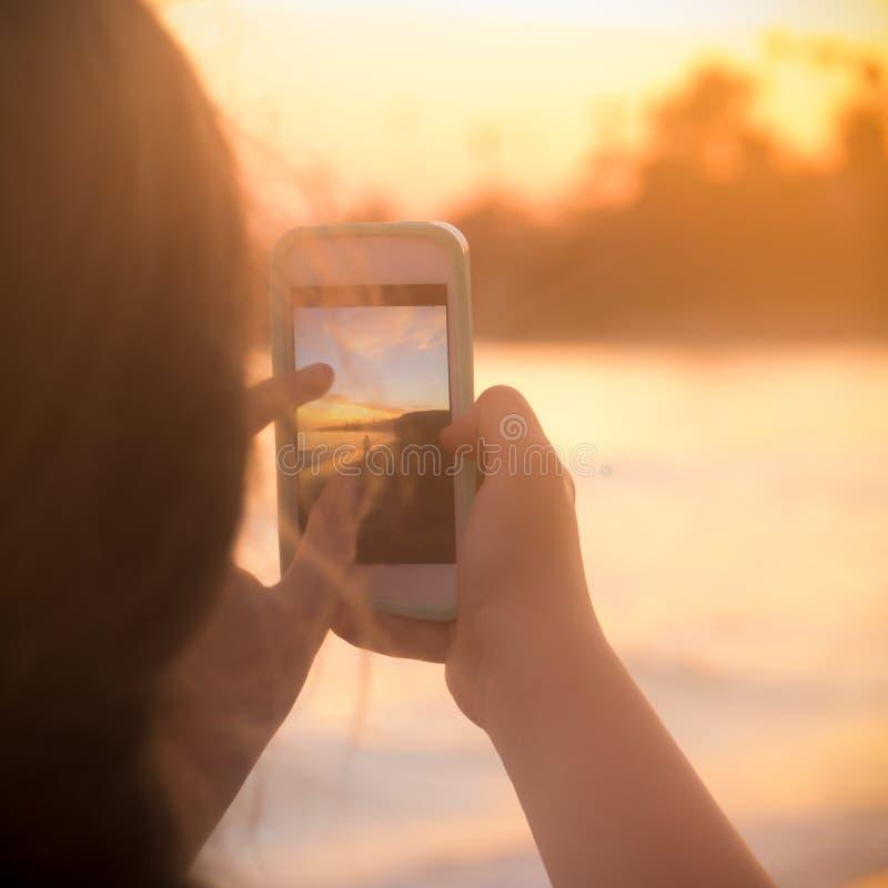 La mujer joven toma la foto elegante del teléfono en la puesta del sol en la playa imagen de archivo