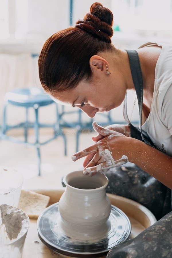La mujer joven trabaja con la rueda de la cerámica fotografía de archivo