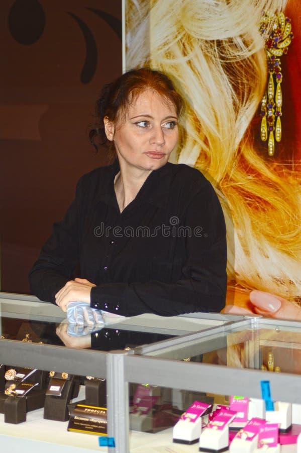 La mujer joven trabaja en una exposición de la joyería JUNWEX Moscú 2014 imagen de archivo libre de regalías