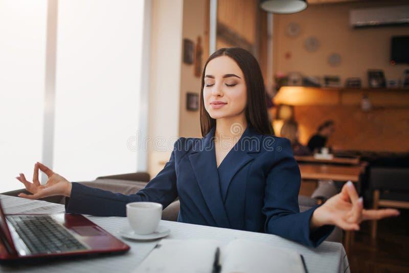 La mujer joven tranquila y pacífica se sienta en la tabla y la meditación Ella mantiene ojos cerrados Cuaderno del ordenador port imagen de archivo