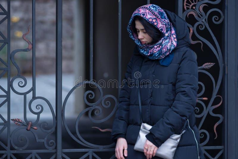 La mujer joven triste se coloca cerca de una puerta del hierro del vintage fotografía de archivo