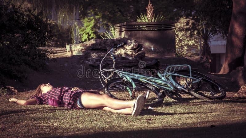 La mujer joven urbana en la bici está teniendo una rotura en la hierba del parque fotos de archivo