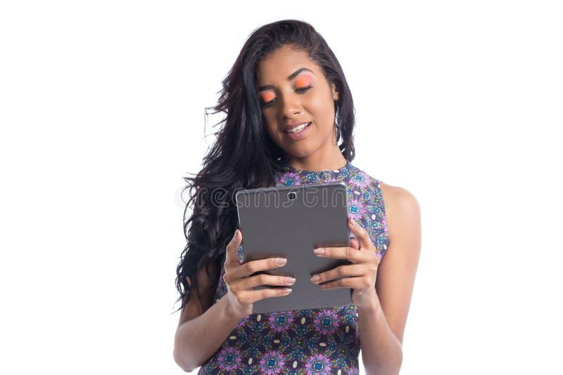 La mujer joven utiliza la tableta digital Muchacha brasileña negra que lleva al su imagen de archivo libre de regalías