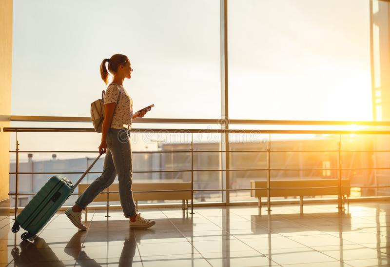 La mujer joven va en el aeropuerto en la ventana con la maleta que espera imágenes de archivo libres de regalías