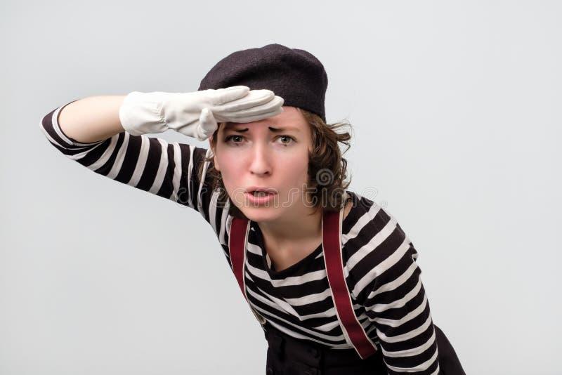 La mujer joven vestida como imita lookingfar lejos, buscando para algo fotos de archivo