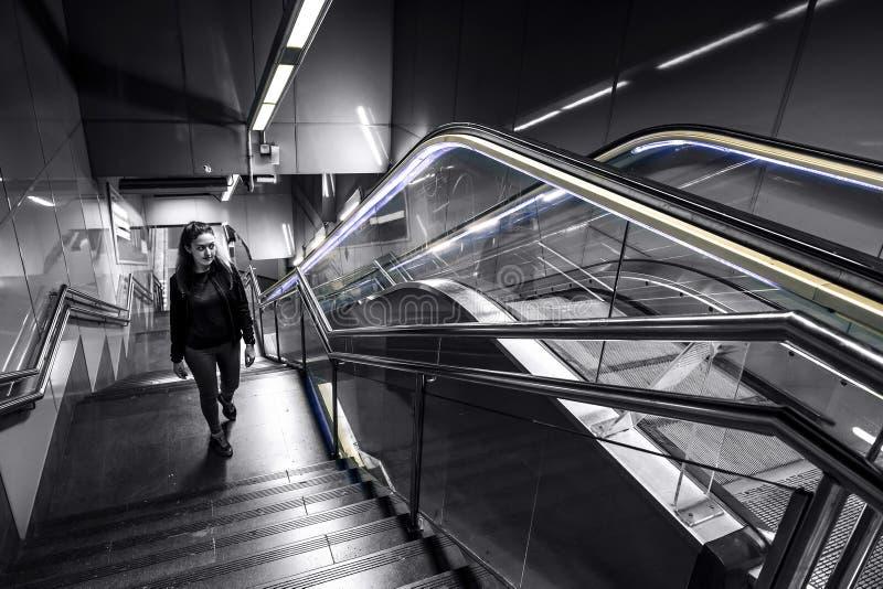 La mujer joven y atractiva va para arriba las escaleras en metro de la estación a la salida imagen de archivo libre de regalías