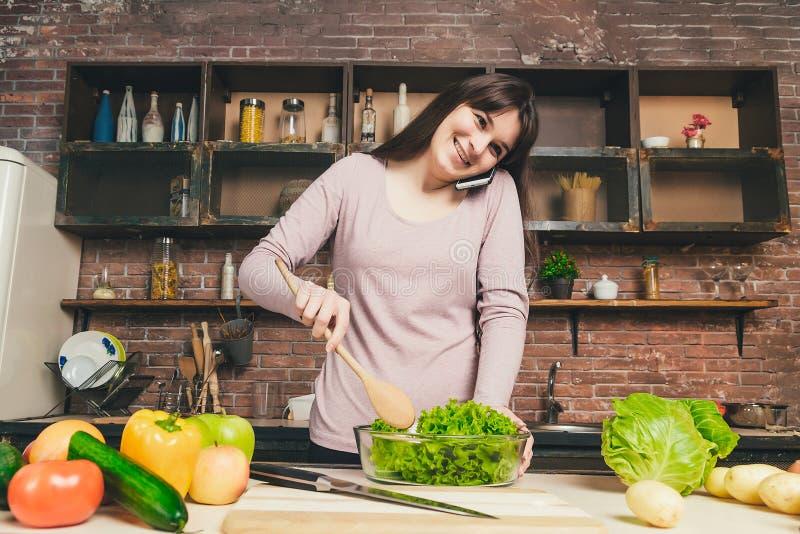 La mujer joven y bonita habla en un teléfono móvil en la cocina mientras que prepara la cena mientras que se coloca en la cocina fotos de archivo