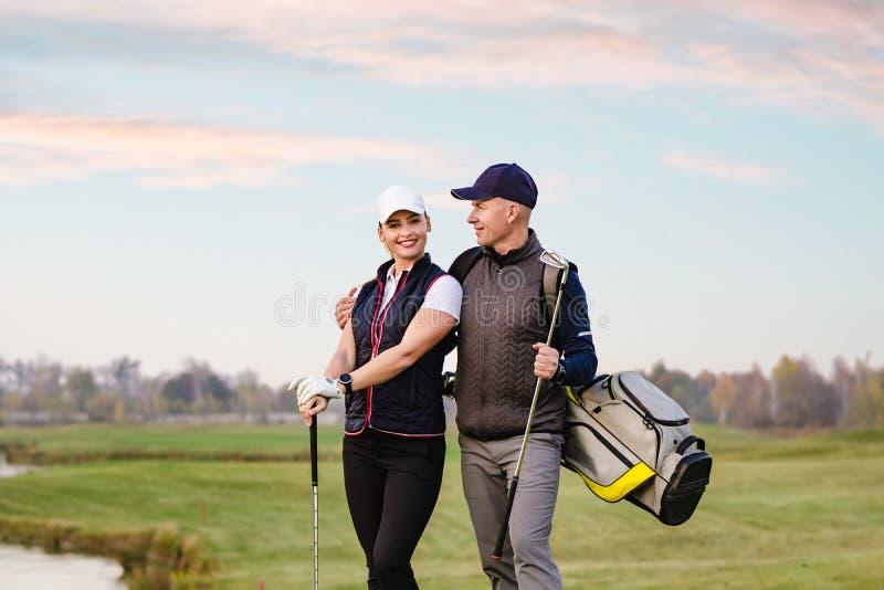 La mujer joven y el hombre están jugando a golf fotografía de archivo libre de regalías