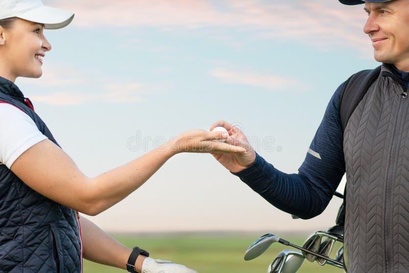 La mujer joven y el hombre están jugando a golf fotos de archivo