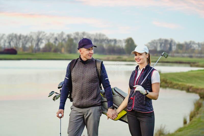 La mujer joven y el hombre están jugando a golf fotografía de archivo