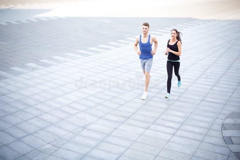 La mujer joven y el hombre que corren en ciudad copian el espacio foto de archivo