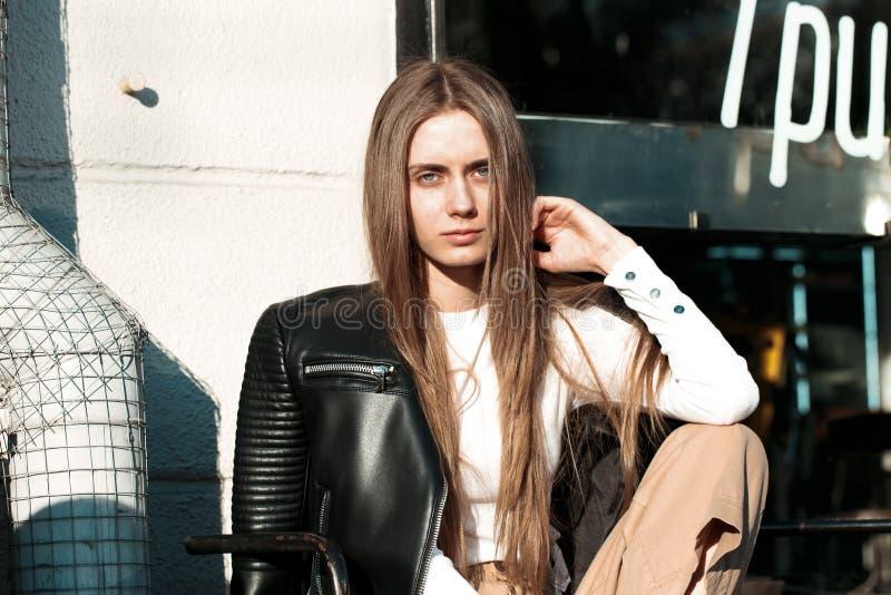 La mujer joven y hermosa se está sentando en un banco en la calle y está presentando para la cámara imagenes de archivo