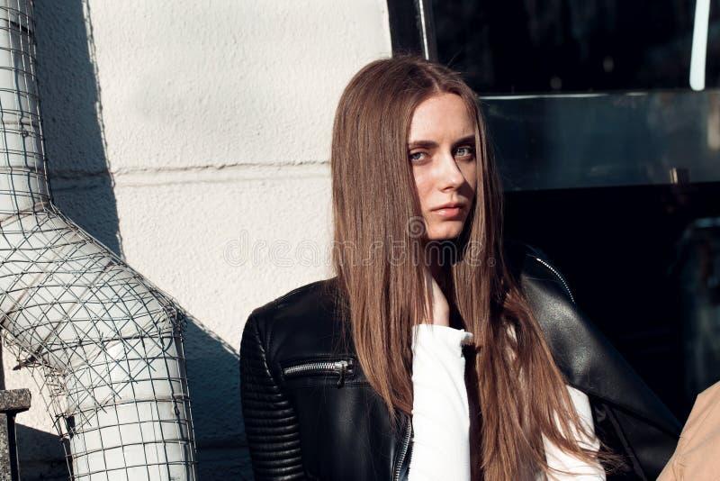 La mujer joven y hermosa se está sentando en un banco en la calle y está presentando para la cámara fotos de archivo libres de regalías