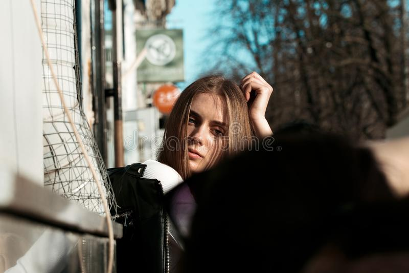 la mujer joven y hermosa se está sentando en un banco en la calle y está presentando para la cámara fotografía de archivo libre de regalías