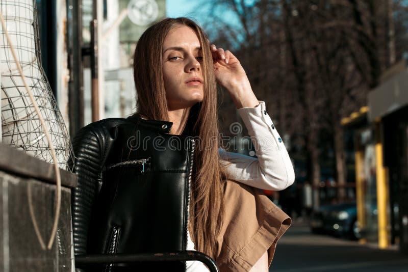 La mujer joven y hermosa se está sentando en un banco en la calle y está presentando para la cámara foto de archivo