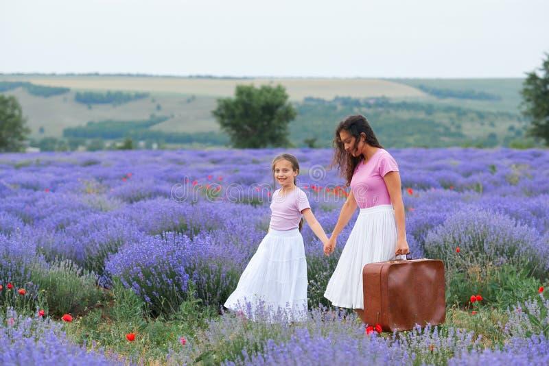 La mujer joven y la muchacha est?n caminando a trav?s del campo de flor de la lavanda, paisaje hermoso del verano imagen de archivo libre de regalías