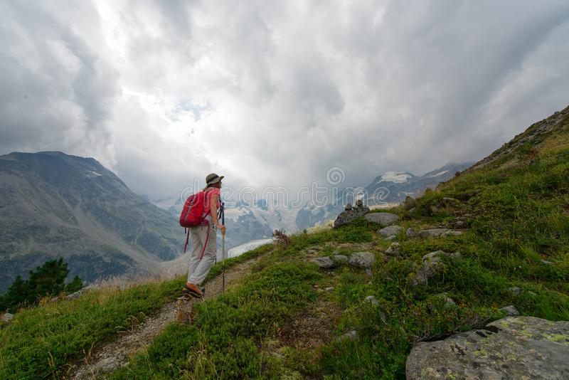 La mujer jubilada practica un alza en las altas montañas imagen de archivo