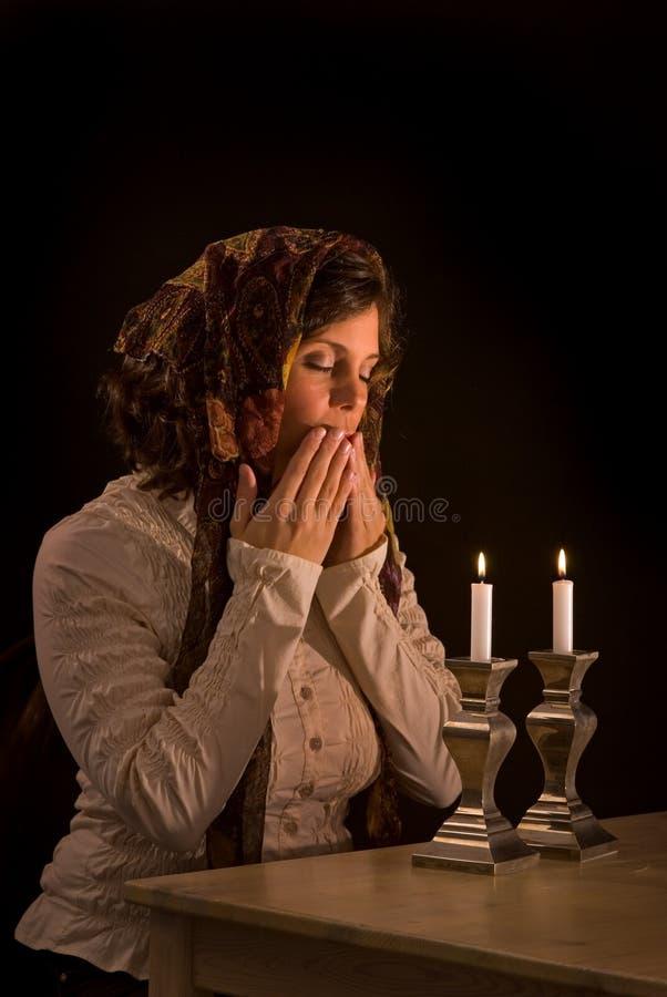 La mujer judía ruega sobre velas del Sabat fotos de archivo