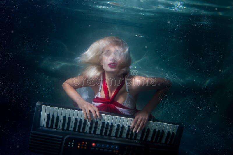 La mujer juega el salto de la música debajo del agua imagenes de archivo