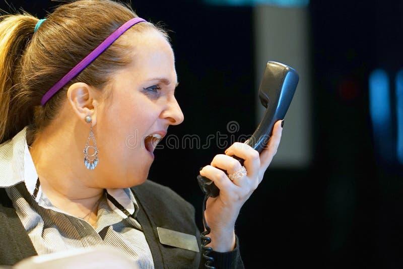 La mujer jura con el cliente por el teléfono foto de archivo libre de regalías