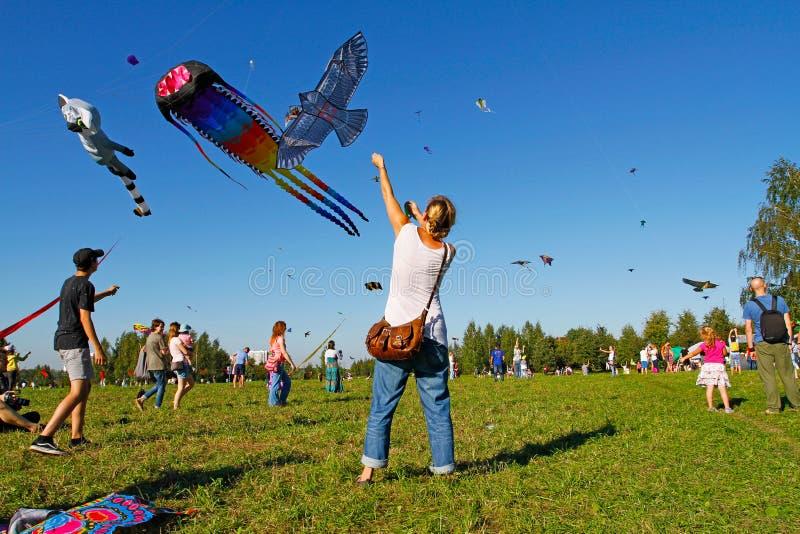 La mujer lanza una cometa en el cielo en el festival de la cometa en el parque Tsaritsyno en Moscú imagen de archivo