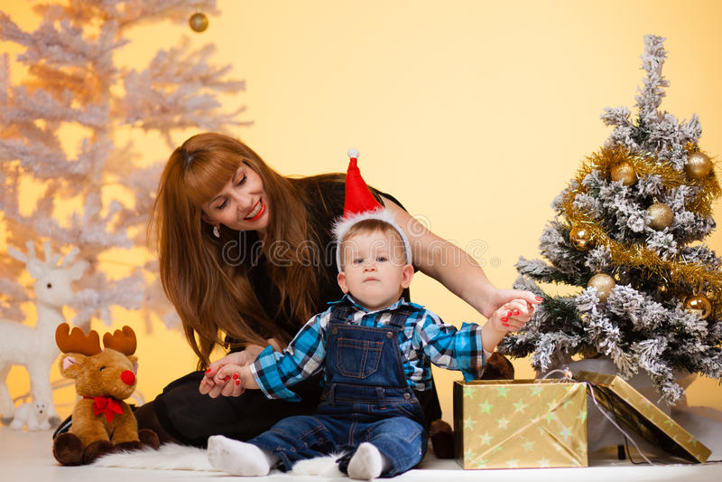 La mujer larga del pelo con el bebé cerca del árbol de navidad abre un regalo imagenes de archivo