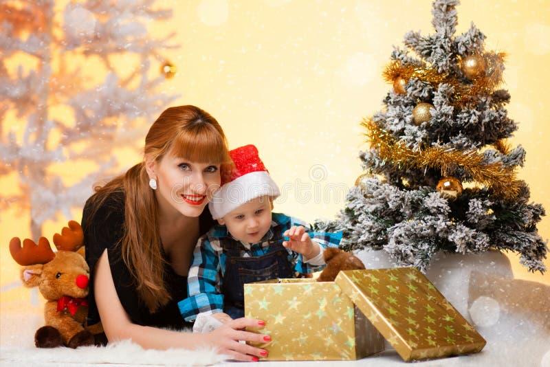 La mujer larga del pelo con el bebé cerca del árbol de navidad abre un regalo imágenes de archivo libres de regalías