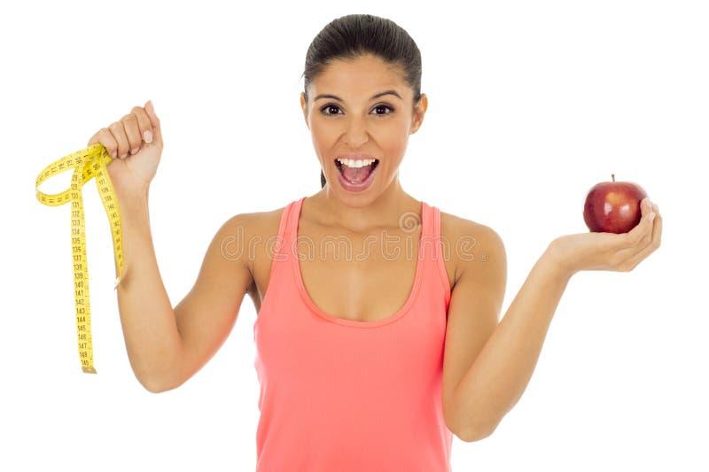 La mujer latina del deporte en la ropa de la aptitud que sostiene la fruta de la manzana y la medida graban la sonrisa feliz imágenes de archivo libres de regalías