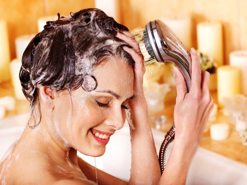 La mujer lava su cabeza en el cuarto de baño. imagenes de archivo