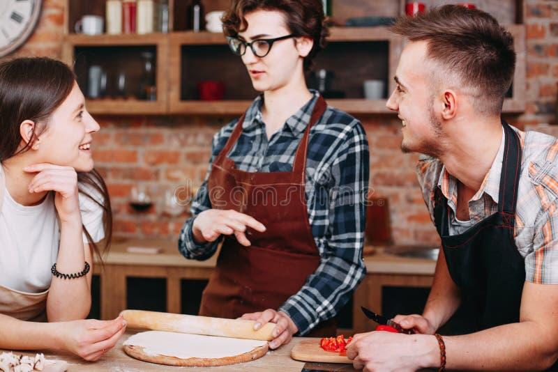 La mujer le enseña a los amigos que hacen la pasta de la pizza foto de archivo libre de regalías