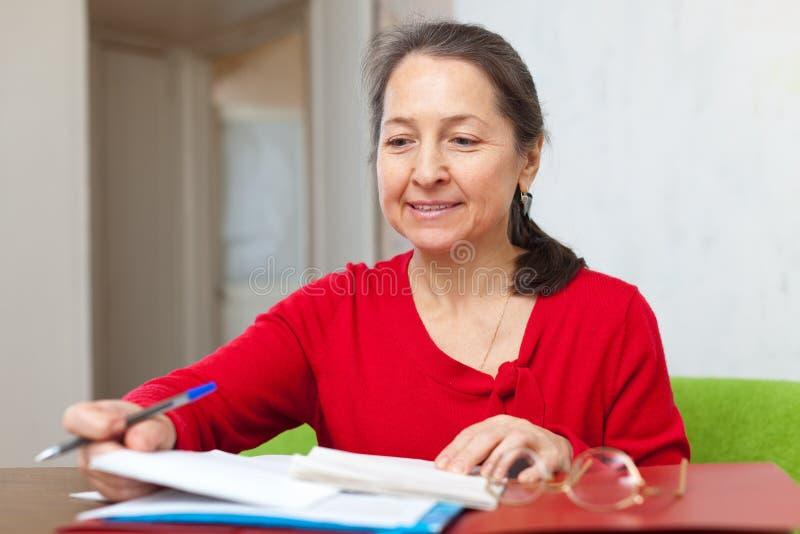La mujer lee documentos en casa foto de archivo libre de regalías